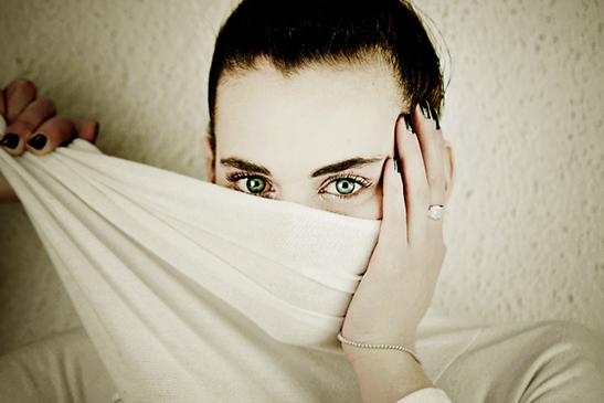 シーツで顔を隠す女性