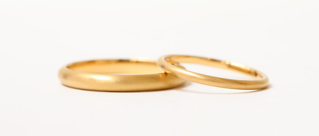 K18イエローゴールドの指輪が二本重なり合う画像 甲丸リングの表面にはマットの加工がしてある