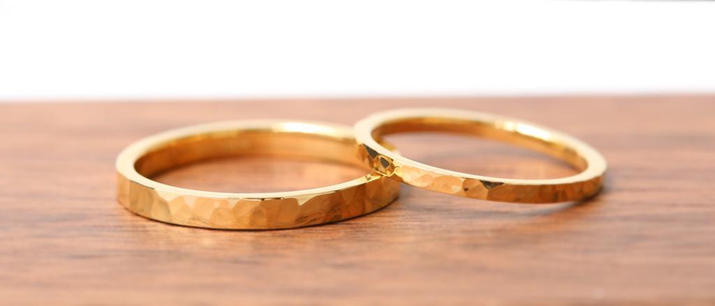 イエローゴールドのフラットリングが2本横に並んで重なり合っている写真 左の方が少しリングの幅が太く、リングの表面には槌目の模様が入っている